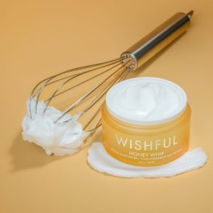 HUDA BEAUTY WISHFUL whip kitchen utensil with Wishful Honey Whip Peptide Moisturizer, creamy blend white color and very thick in consistency, background of image is the same color as the the product a yellow honey color 3rd party people